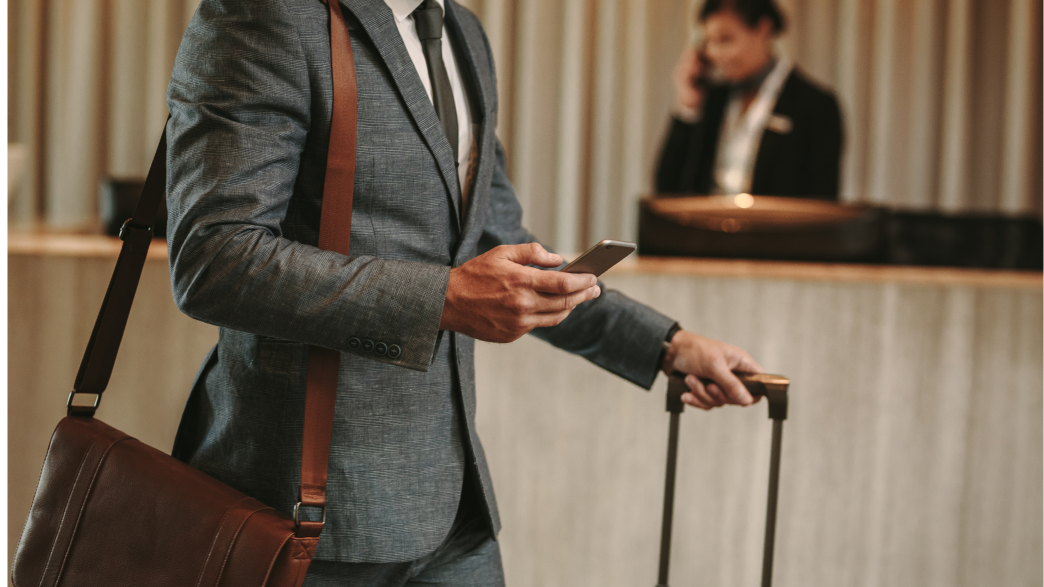 Man in grey suit at the check-in desk with his luggage looking at his phone